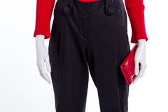 Close up black trousers and red wallet. Black cotton trousers for women. Female fashion style stock photography