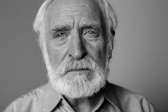 Wrinkled old man expressing emotional pain. Close up black-and-white portrait of sorrowful man looking at camera while standing.  on grey background Stock Photography
