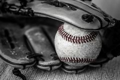 Close up black and white shot of a vintage baseball and glove. Royalty Free Stock Photos