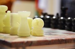 Close-up of black and white soapstone marble chess pieces on chessboard Royalty Free Stock Photo