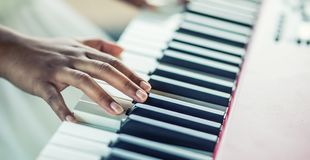 Close-Up a black woman hands playing on piano royalty free stock photography