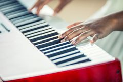 Close-Up a black woman hands playing on piano royalty free stock images