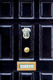 Close up of black wooden entrance door with brass letterbox in traditional style, Dublin Ireland. Royalty Free Stock Photo