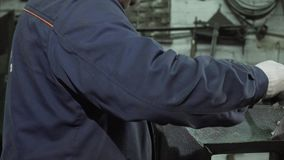 Close Up Of Blacksmith In Protective Clothing Using Tools And A Welding Machine