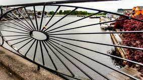 Close up of a blacksmith handrail with a padlock on a bridge over the river Shannon. Boats anchored at the dock in the town of Athlone in the county of stock photo