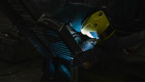 Close-up blacksmith welder in protective mask works with metal using a welding machine, bright sparks and flashes. 4K