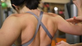 Close-up of the blades. Slender girl shakes the muscles of the arms and back in the gym 4K Slow Mo stock video footage