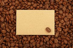 Kraft paper sign on brown roasted coffee beans. Close up blank brown kraft paper sign with copy space on background of roasted coffee beans, elevated top view Royalty Free Stock Images