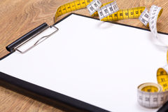 Close up of blank clipboard and measure tape Stock Photo