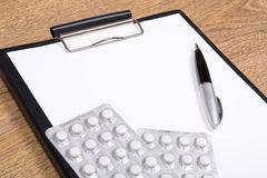 Close up of blank clipboard, pen and pills Royalty Free Stock Photos