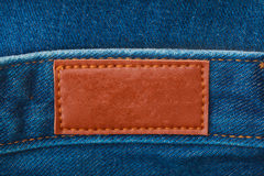 Close up of blank leather label on blue denim. For graphic design or branding Stock Image