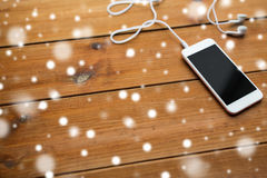 Close up of blank smartphone and earphones on wood Stock Image