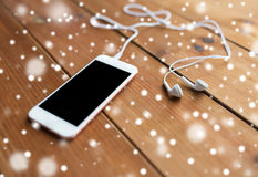 Close up of blank smartphone and earphones on wood Stock Photo