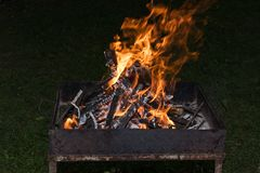 Blazing Fire in Grill. Close-up of blazing fire in rustic BBQ grill at evening royalty free stock photo