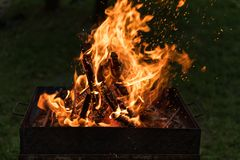 Blazing Fire in Grill. Close-up of blazing fire in rustic BBQ grill at evening royalty free stock images