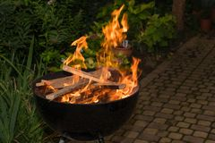 Blazing Fire in Grill. Close-up of blazing fire in rustic BBQ grill at evening stock photo