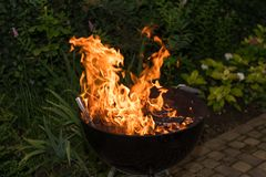 Blazing Fire in Grill. Close-up of blazing fire in rustic BBQ grill at evening royalty free stock photos