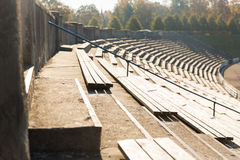 Close up of bleachers with benches on stadium. Sport and architecture concept - close up of stands or rows of benches on stadium stock image