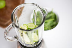 Close up of blender jar and green vegetables Stock Images