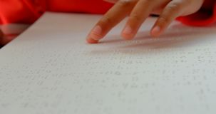 Close-up of blind Asian schoolboy hand reading a braille book in classroom at school 4k stock footage