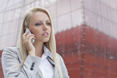 Close-up of blond businesswoman conversing on mobile phone with office building in background Stock Photo