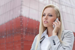 Close-up of blond businesswoman conversing on mobile phone with office building in background Royalty Free Stock Photos