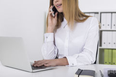 Close up of a blond girl on her phone in office Royalty Free Stock Image