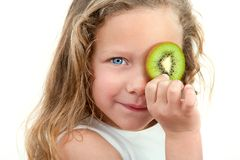 Close up of blond girl holding fruit. Close up Portrait of cute little girl holding fruit in front of eye. Isolated on white background Royalty Free Stock Image