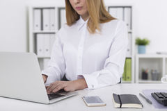 Close up of blond girl typing. Close up of a young woman with long blond hair typing on her laptop keyboard. There a smartphone and a notebook on her desk royalty free stock photography