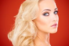 Close Up of Blond Woman Against Red Background Royalty Free Stock Image