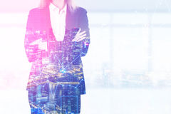 Close up of a blond woman with crossed arms standing in an office with panoramic windows. Stock Photos