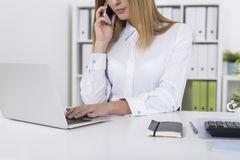 Close up of a blond woman on her phone in office Royalty Free Stock Photography