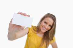 Close-up of a blond woman showing a white card Royalty Free Stock Photography