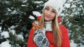 Close up blond woman walks, eat gingerbread in winter landscape stock footage