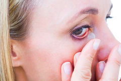 Close up of blonde applying contact lens Stock Photo