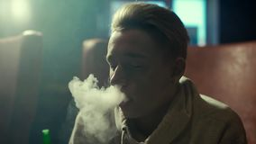Close-up blonde guy with an earring in ear exhales thick smoke in slow motion. Close-up attractive blonde guy with an earring in his ear smoking a hookah and stock video