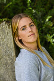 Close-up of blonde leaning against wooden gatepost Royalty Free Stock Photos