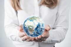 Close-up of blonde's hands who holds the globe with Africa, Europe and Asia hemisphere. A woman dressed in formal clothes. A light Stock Images