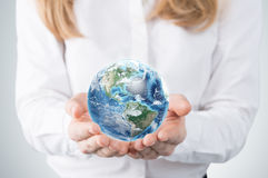Close-up of blonde's hands who holds the globe with western hemisphere. A woman dressed in formal clothes. Stock Photos