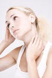 Close up of a blonde woman massaging her neck Royalty Free Stock Photo