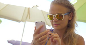 Close-up of blonde woman using smartphone. Close-up of blonde woman in mirrored sunglasses using smartphone with stylus and smiling stock video