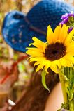 Close-up of blooming vibrant yellow sunflower with blurred woman wearing blue summer hat drinking cocktail with red straw on. The background royalty free stock photo