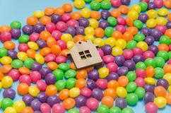 Blue background with candy and wooden toy house. Close-up, blue background with candy and wooden toy house, mortgage, housing, insured Royalty Free Stock Photography