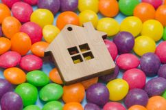 Blue background with candy and wooden toy house. Close-up, blue background with candy and wooden toy house, mortgage, housing, insured Royalty Free Stock Image