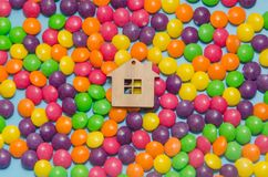 Blue background with candy and wooden toy house. Close-up, blue background with candy and wooden toy house, mortgage, housing, insured Royalty Free Stock Photo