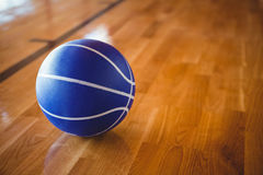 Close up of blue basketball on hardwood floor Stock Photos