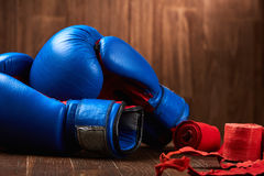 Close-up of the blue boxing gloves and red bandage on wooden background. Horizontal photo of the bright colorful sportwear and sportive accessories. Sportive Royalty Free Stock Photos