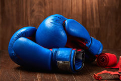 Close-up of the blue boxing gloves and red bandage on wooden background. Horizontal photo of the bright colorful sportwear and sportive accessories. Sportive Royalty Free Stock Images