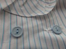 Close up of blue Buttons on a stripped blouse. Close up of a blue stripped blouse, the buttons, thread and a bit of the collar Royalty Free Stock Photos