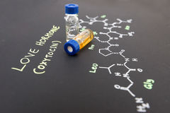 Close-up blue cap sample vial on paper with chemical formula of Stock Image